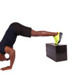 Young man doing pike push ups feet elevated