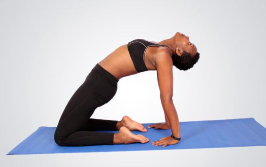 Young woman doing yoga pose kneeling on yoga mat