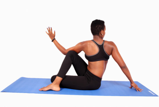 Young woman twisting torso doing yoga