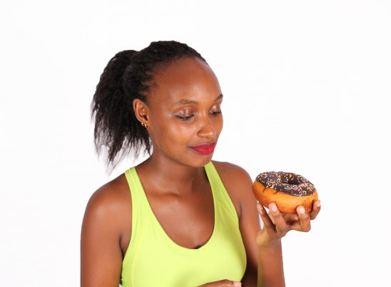 A healthy woman tempted to eat unhealthy doughnut