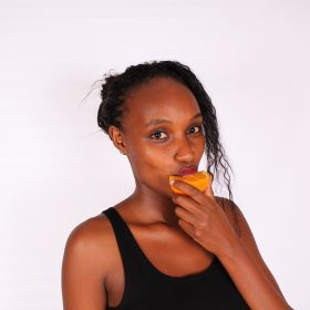 Young African Woman Eating Citrus Orange Fruit