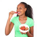 African woman eating strawberries from a bowl