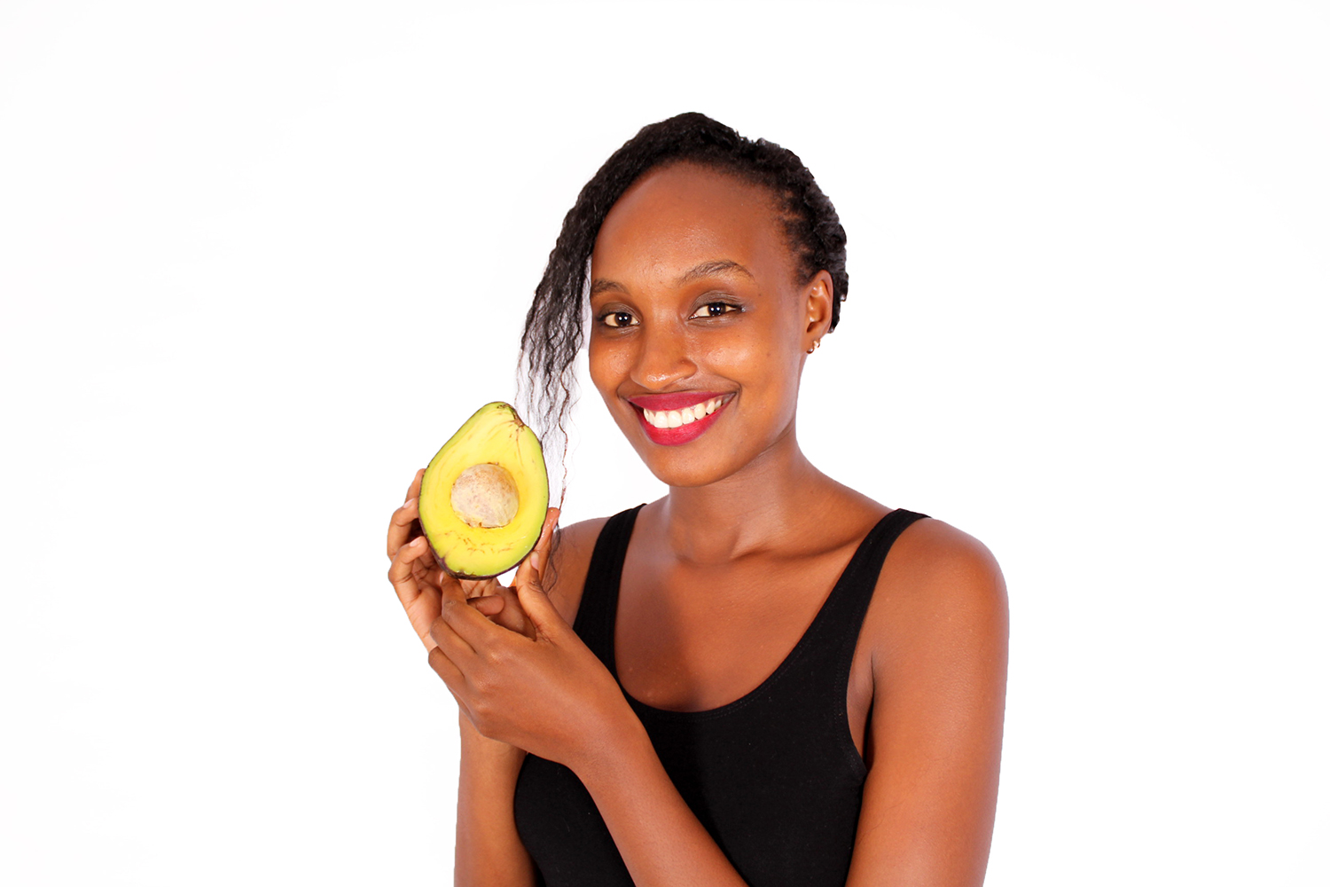 African woman holding half avocado slice