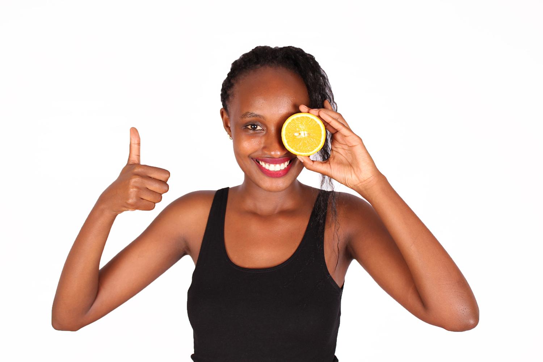 Beautiful woman covering eye with half orange slice
