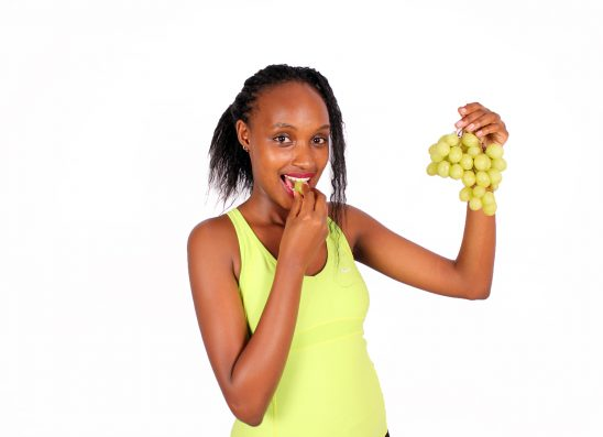 Beautiful woman eating green grape