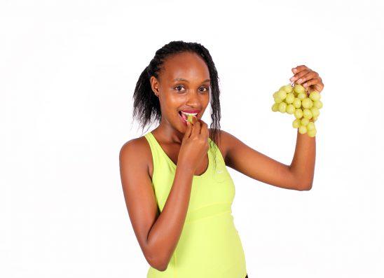 Beautiful woman eating green grape