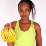 Beautiful woman holding banana bunch