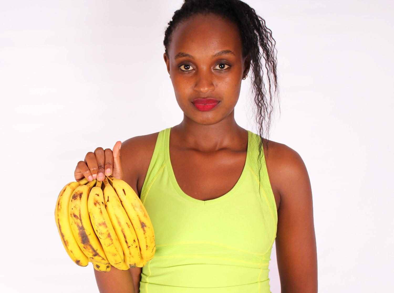 Beautiful woman holding banana bunch