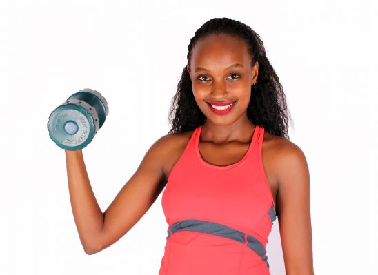 Beautiful woman lifting dumbbell with one arm