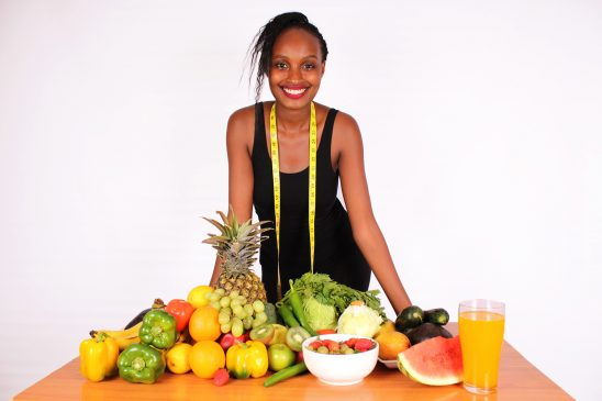 Beautiful woman standing behind table with frutis and vegetables