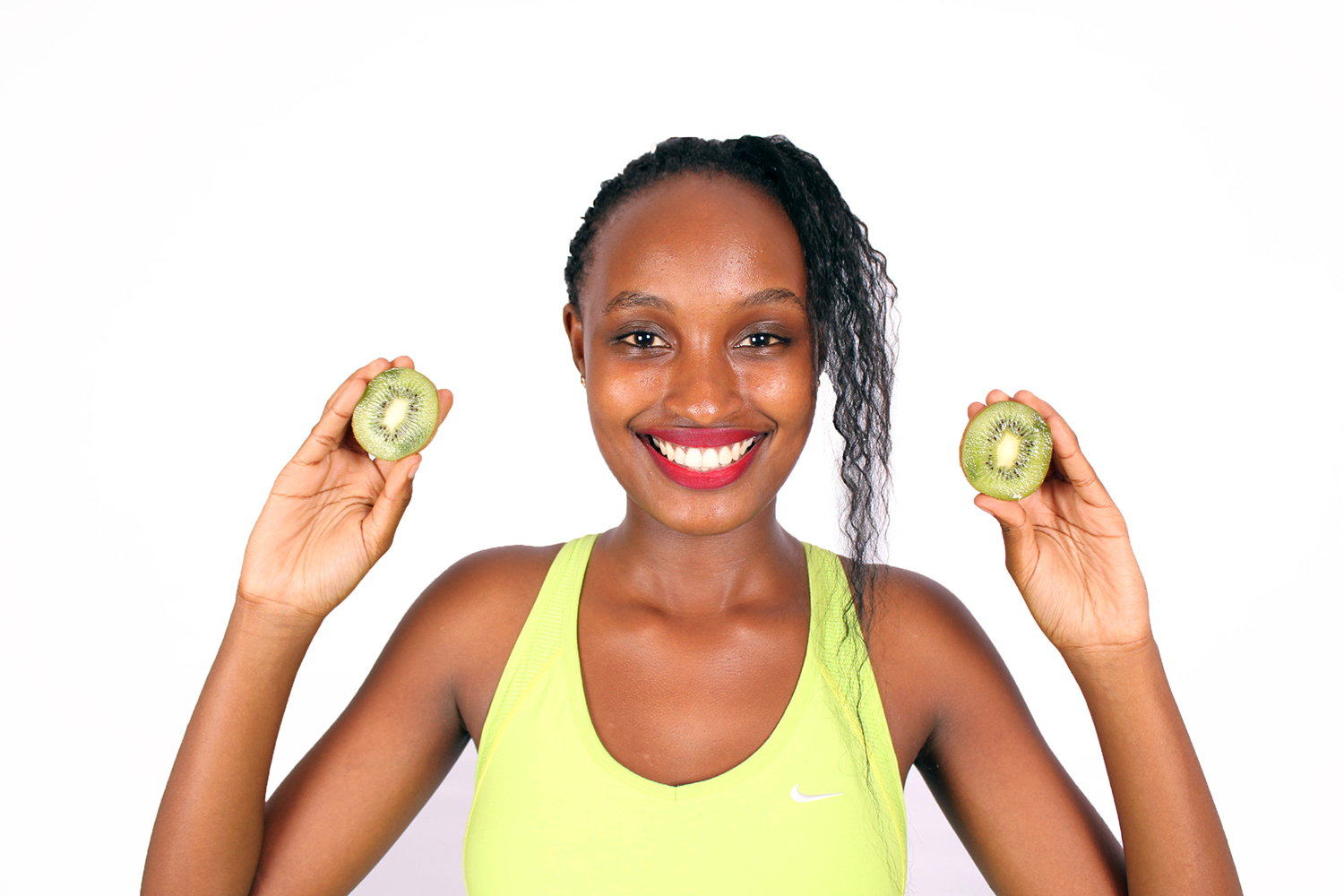 Smiling Woman Holding Two Slices of Kiwi Fruit