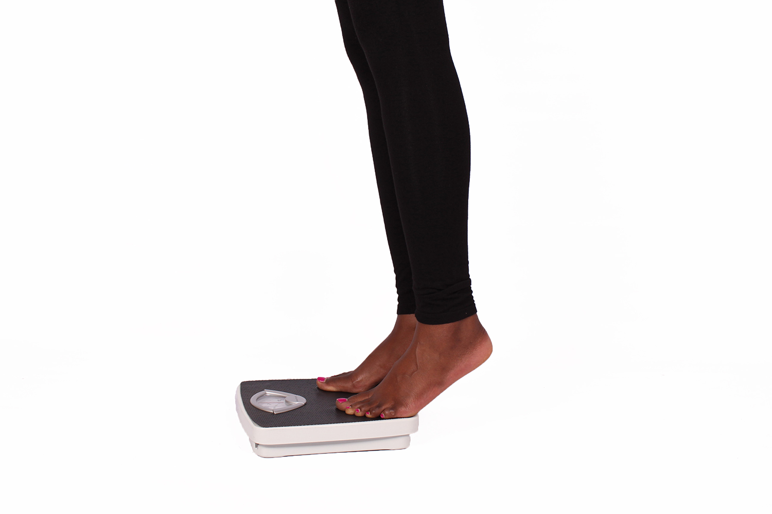 Legs of Woman Stepping on Weigh Scale to Measure Weight