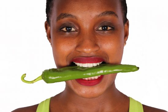 Close up woman bitting green pepper