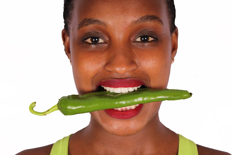 Close up woman bitting green pepper