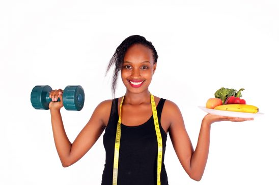 Woman Lifting Dumbbell and Fresh Fruits and Veggies in Plate
