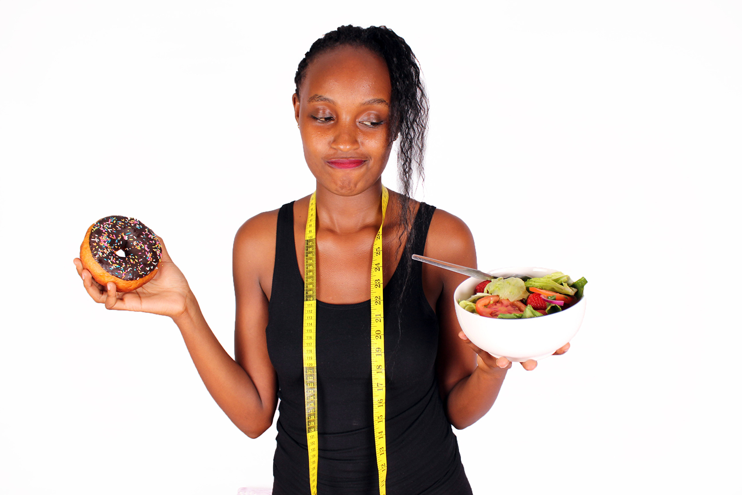 Diet woman holding salad bowl and doughnut