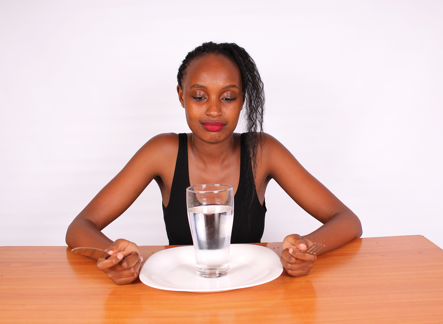 Fasting Concept. Woman Sitting on Table With Plate and Glass of Water