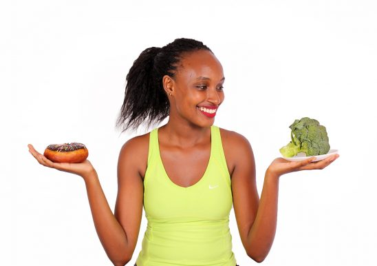 Dieting woman chosing between broccoli and doughnut