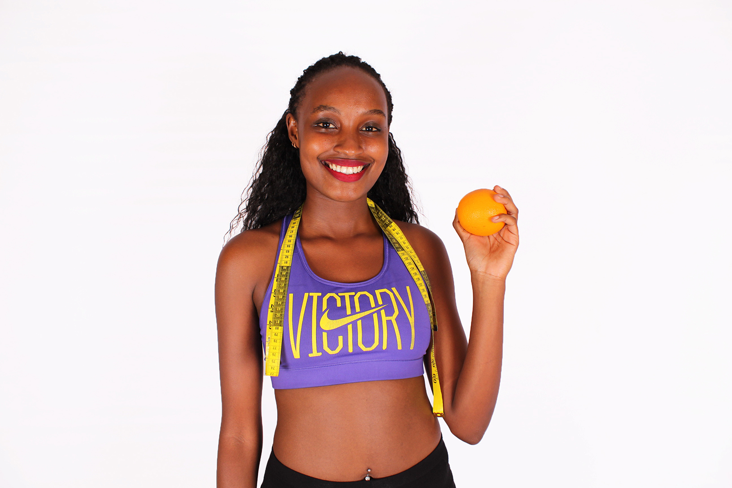 Dieting woman with orange fruit and tape measure
