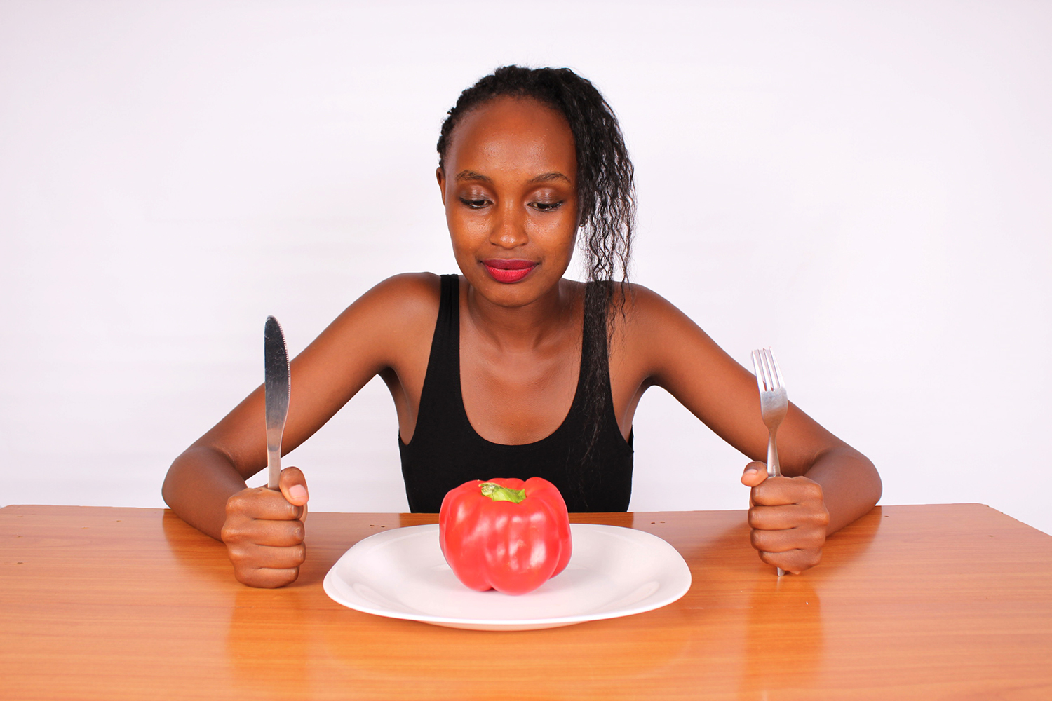 Hungry Dieting Woman Seated on Table With Red Pepper on Plate