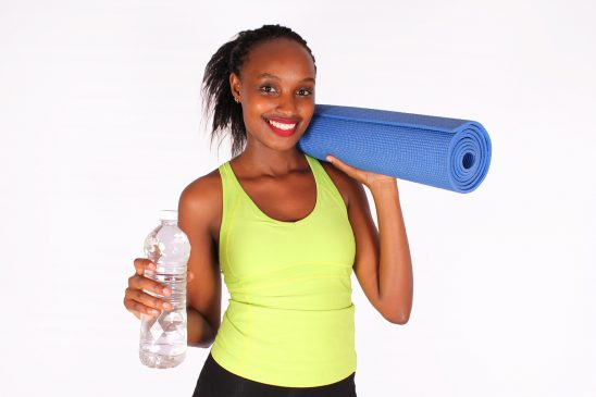 Fit healthy woman with yoga mat and water bottle
