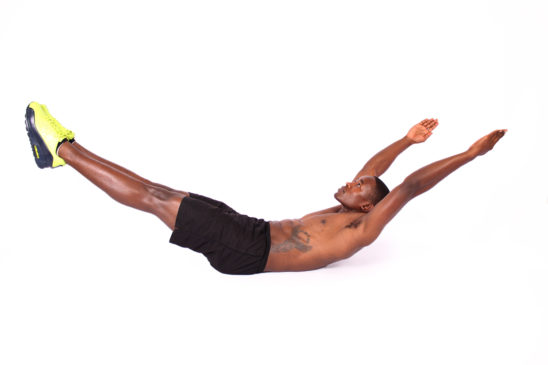 Fit man doing hollow body holds ab exercise