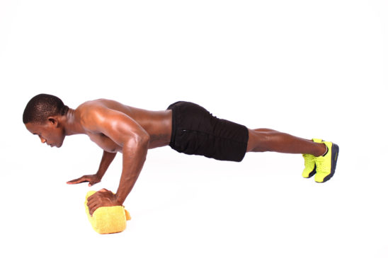 Fitness man doing push ups using towel