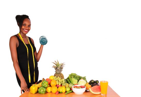 Fitness woman lifting dumbbell standing next table with fruits and vegetables