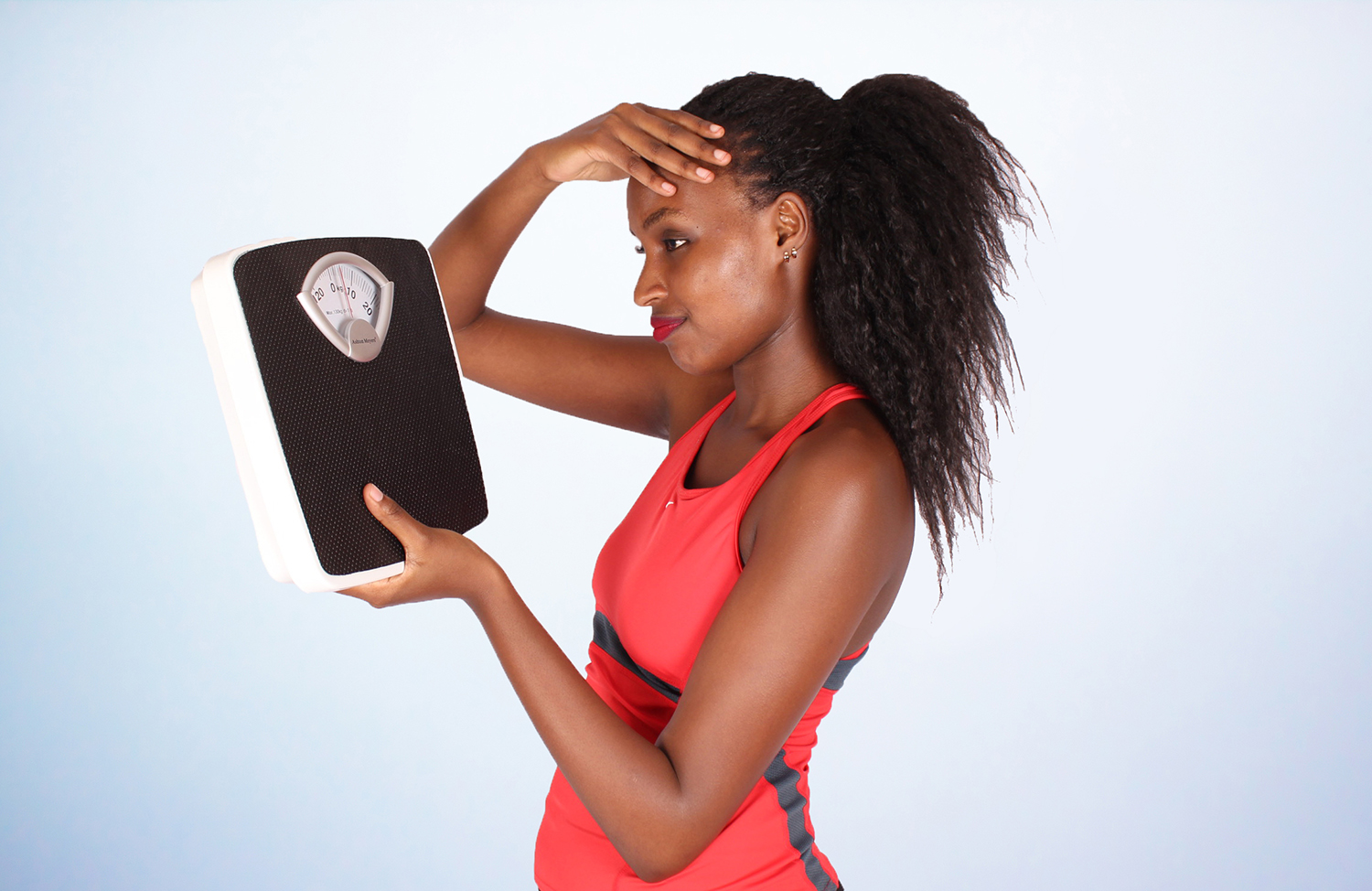 Frustrated woman looking at weight scale