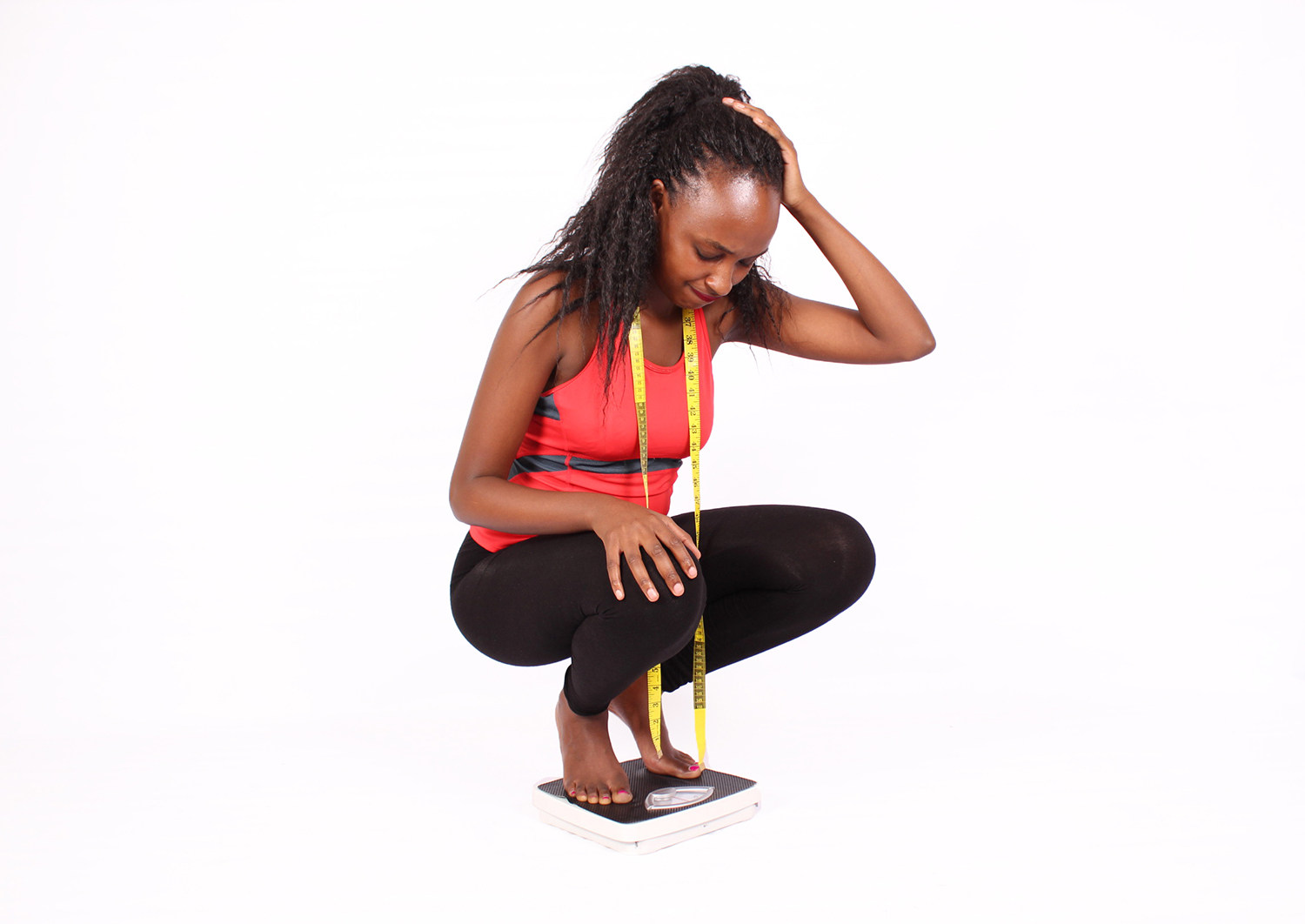 Frustrated woman with tape measure squatting on weigh scale