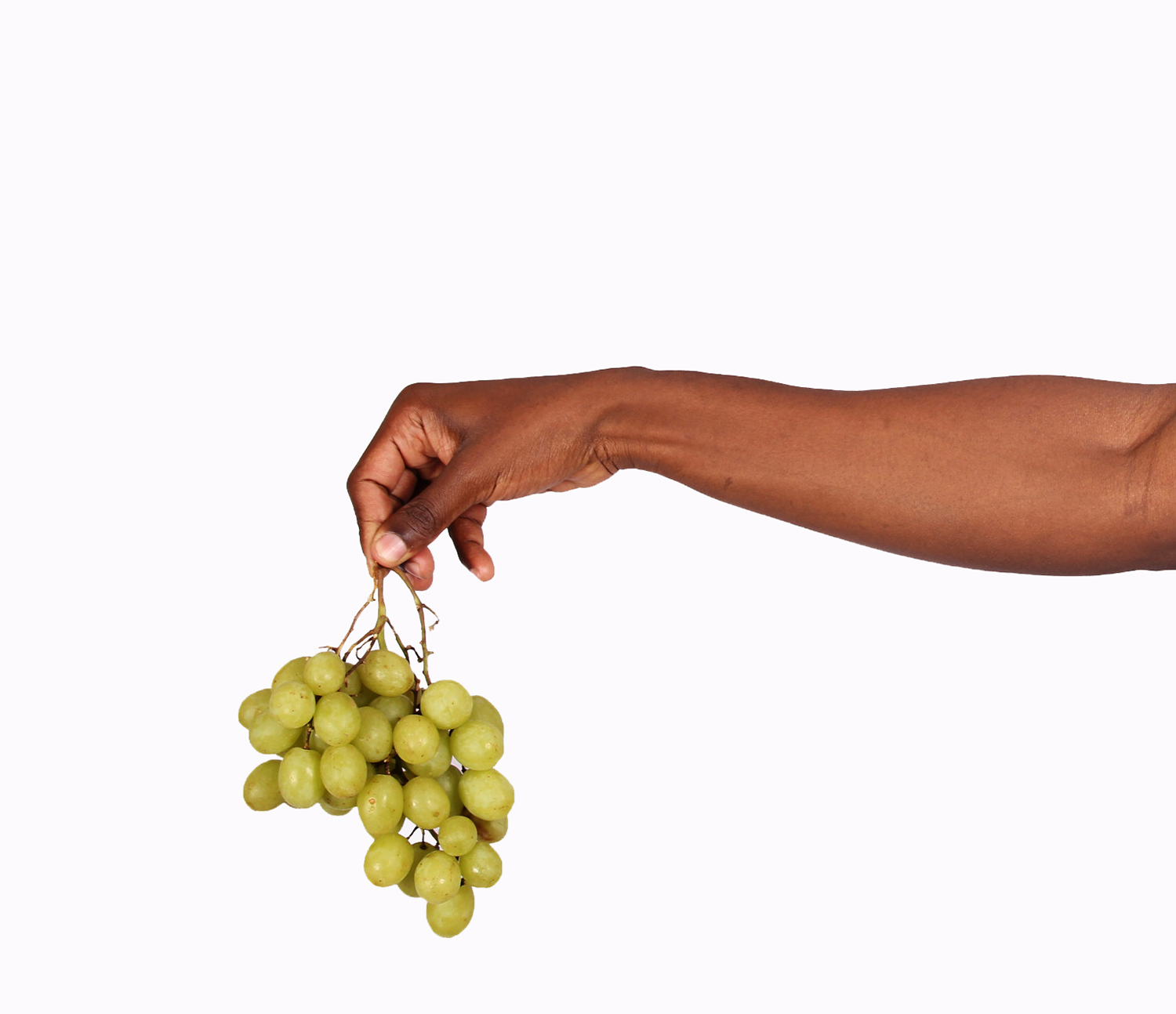 Hand holding green grapes