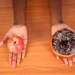 Dieting Concept of Healthy and Unhealthy Foods. Doughnut vs Apple