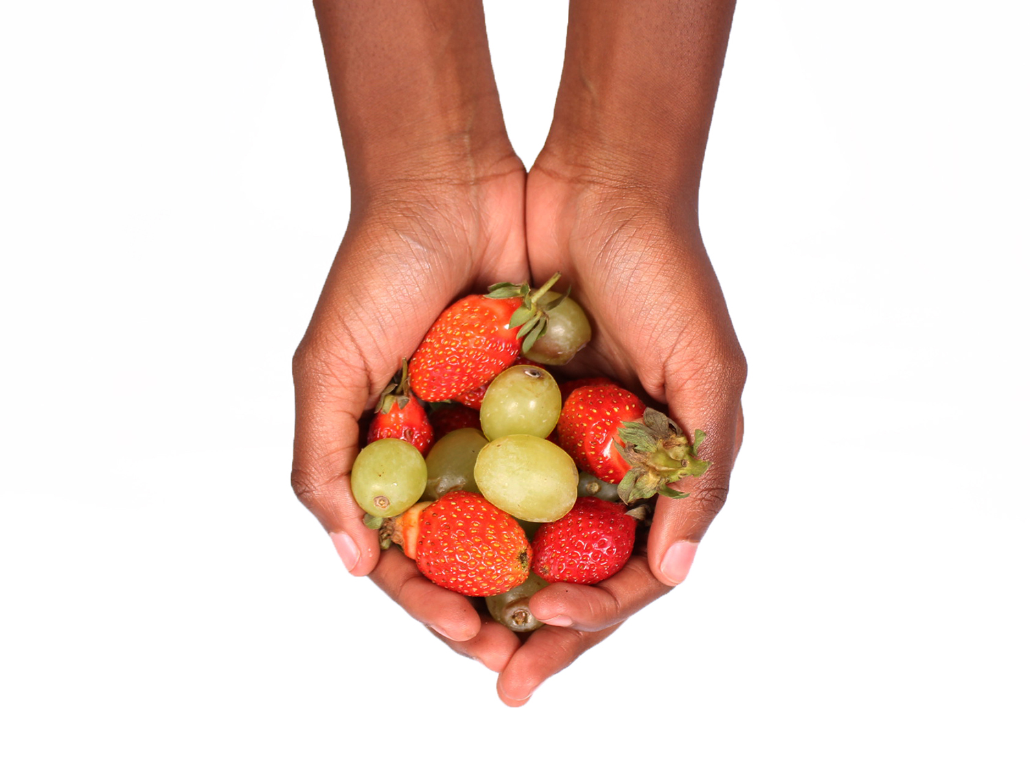 Hands holding strawberries and green grapes