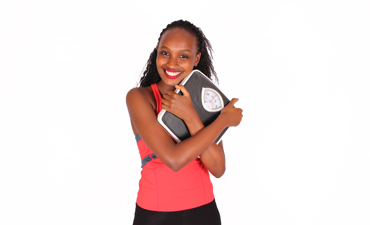 Happy woman hugging weight scale after successful weight loss