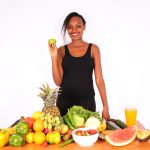Healthy lifestyle woman holding green apple behind table of fruits and vegetables