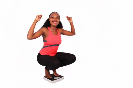 Healthy Woman Celebrating Weight Loss Stepping on Weigh Scale