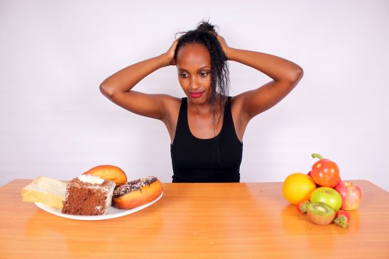 Healthy woman confused with unhealthy foods and healthy food