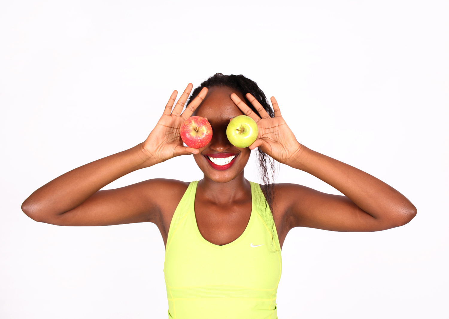 Healthy woman covering eyes with red and green apple