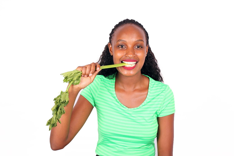 Healthy woman eating celery stalks