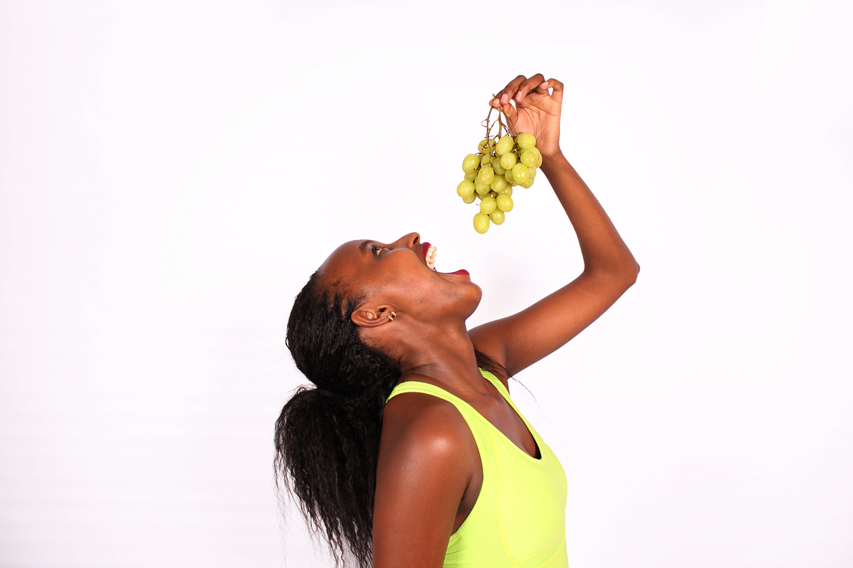 Healthy woman eating green grapes