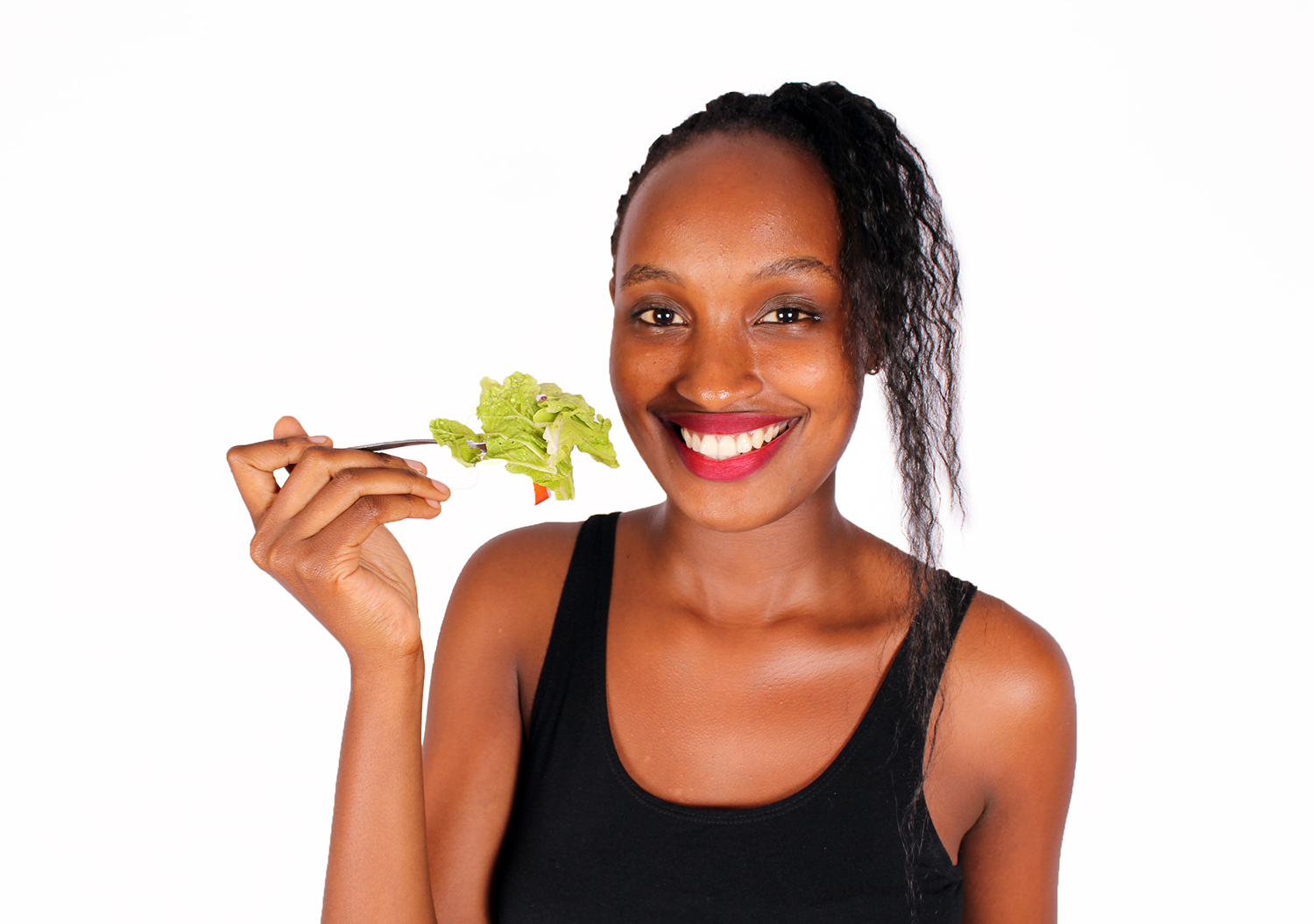 Healthy woman eating raw veggies using folk