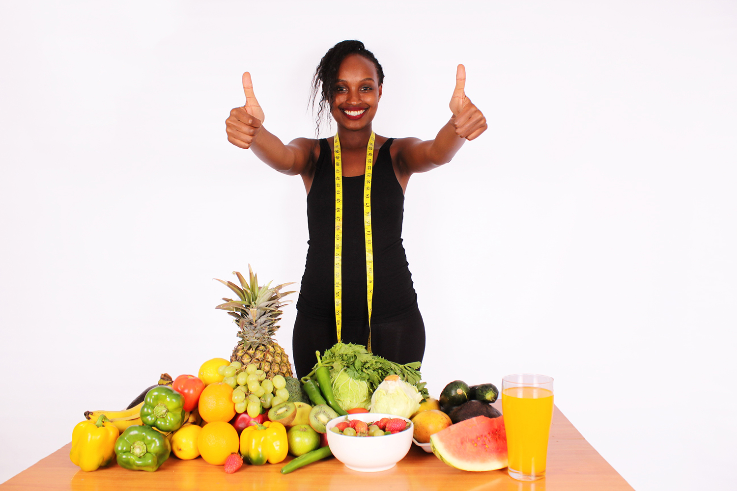 Healthy woman gives thumbs up for fruits and vegetables