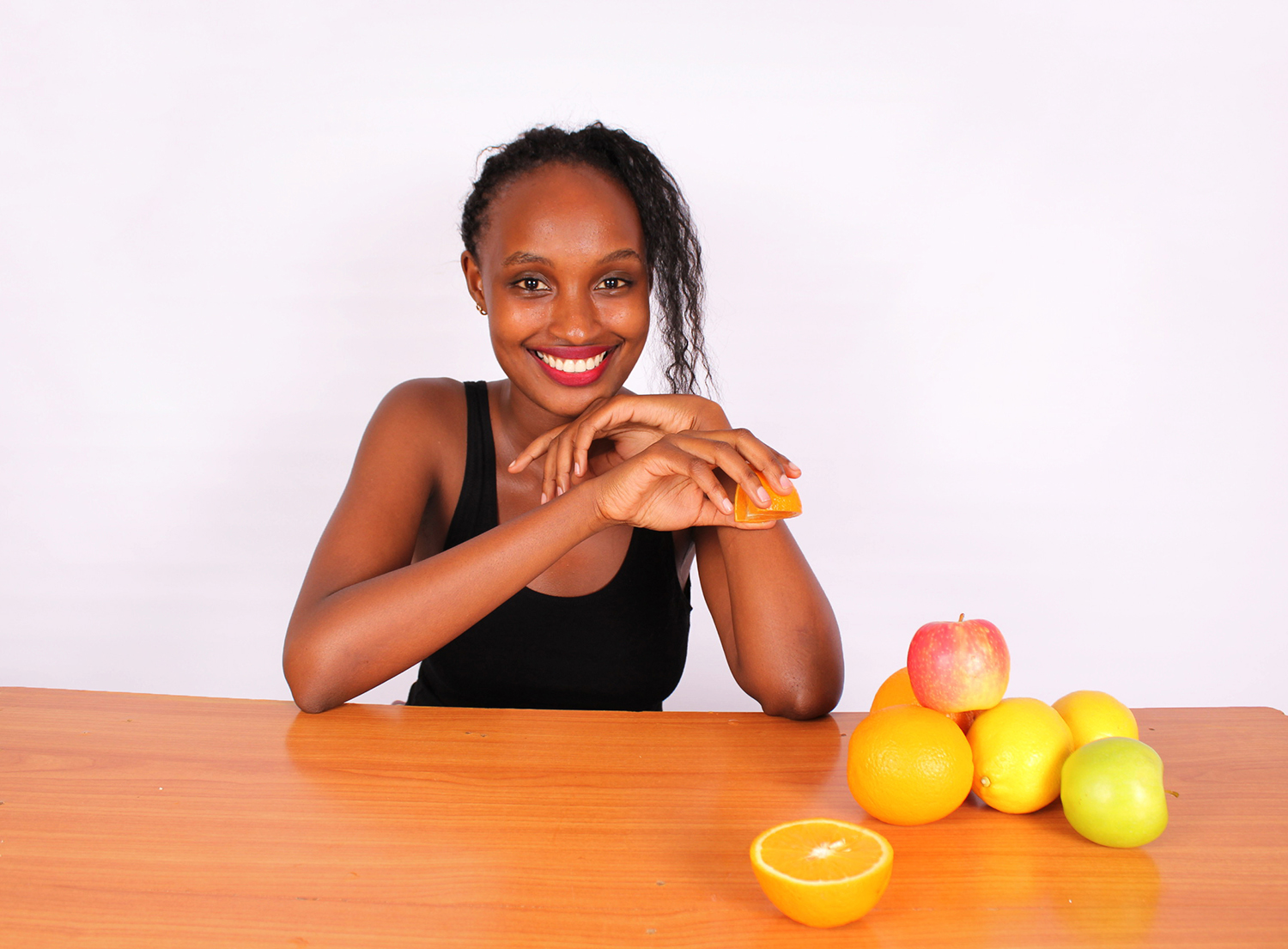 Healthy woman holding orange slice and fruits on table