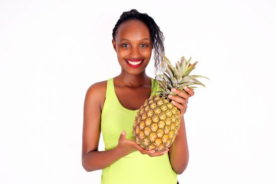 Healthy woman holding pineapple fruit