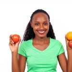 Healthy woman holding tomato orange and apple