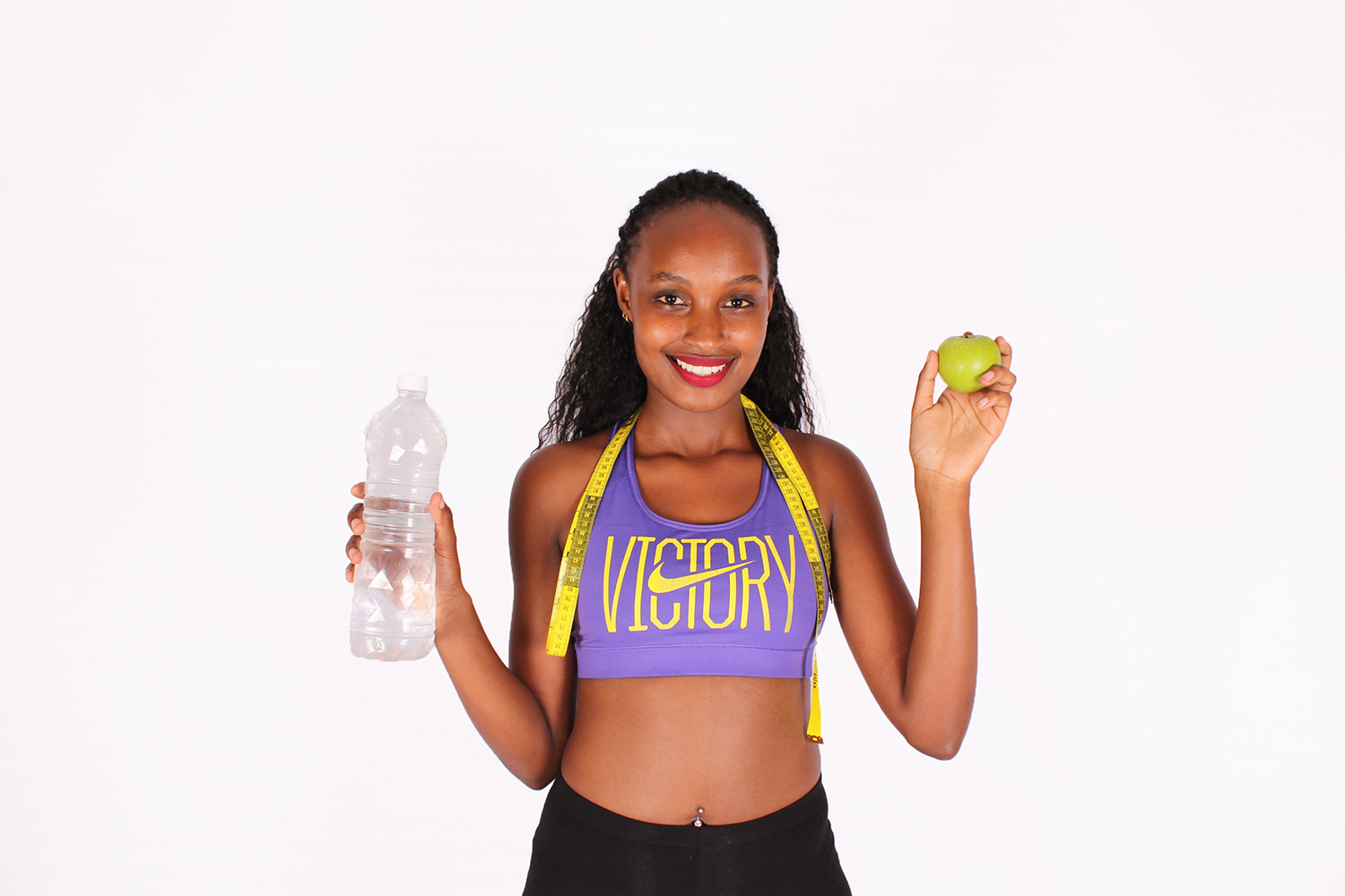 Healthy woman with water bottle green apple and tape measure