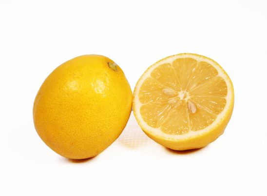 One lemon and half slice on white background