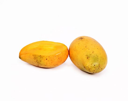 One sliced mango and one mango on white background