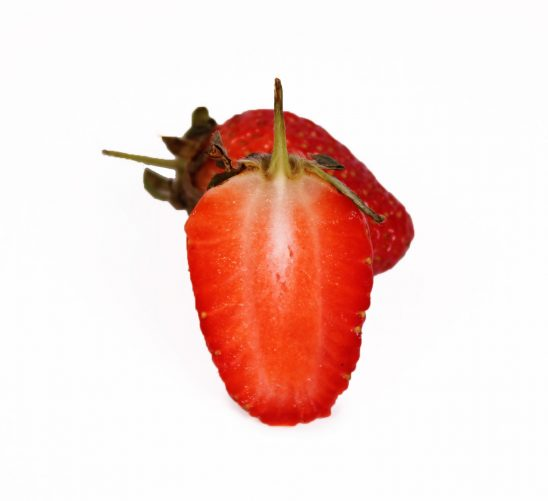 One sliced strawberry and one strawberry on white background