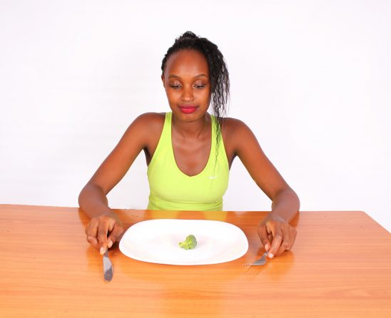 Restrictive Dieting. Woman Eating Small Piece of Broccoli
